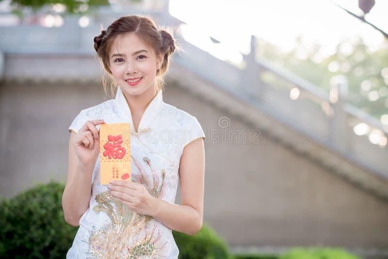 亚裔妇女用中文穿戴拿着对联'愉快' (脊椎 免版税库存图片