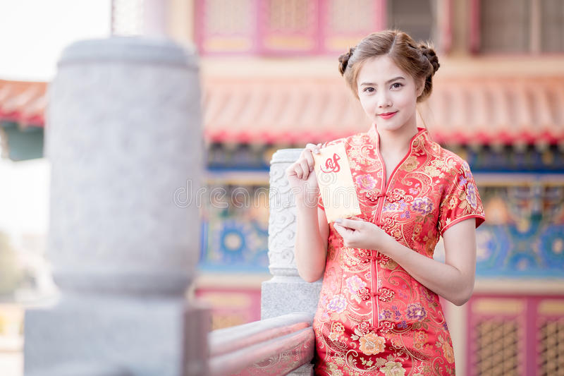 亚裔妇女用中文穿戴拿着对联'愉快' (脊椎 库存图片