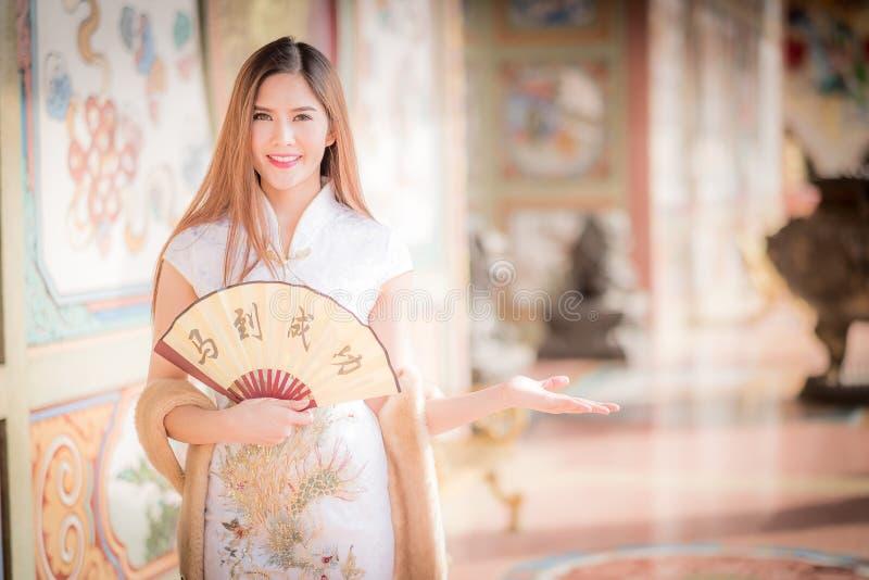 亚裔妇女用中文穿戴拿着对联'成功' (奇恩角 库存图片