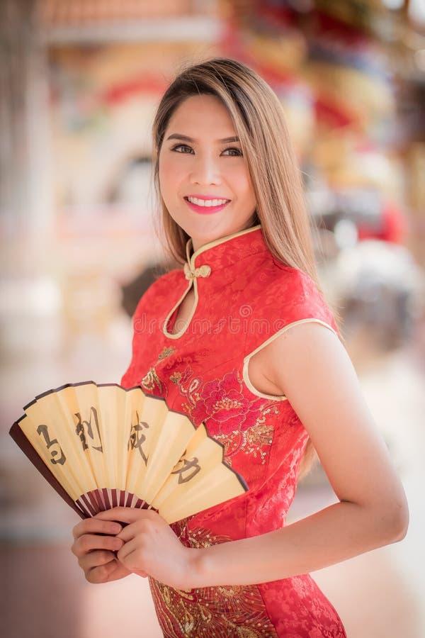 亚裔妇女用中文穿戴拿着对联'成功' (奇恩角 免版税库存图片