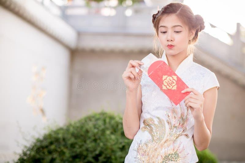 亚裔妇女用中文穿戴拿着对联'赚钱' (C 免版税库存照片