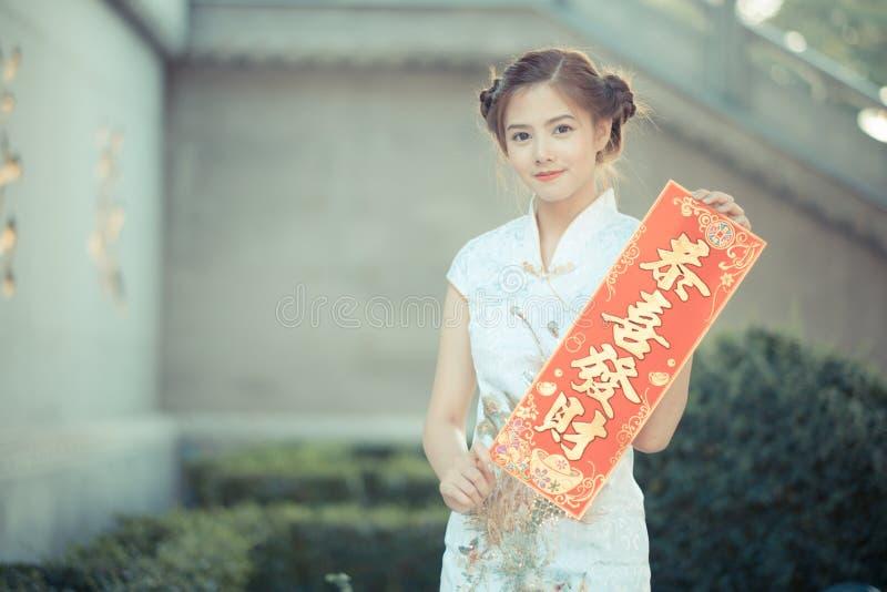 亚裔妇女用中文穿戴拿着对联'赚钱' (C 免版税图库摄影