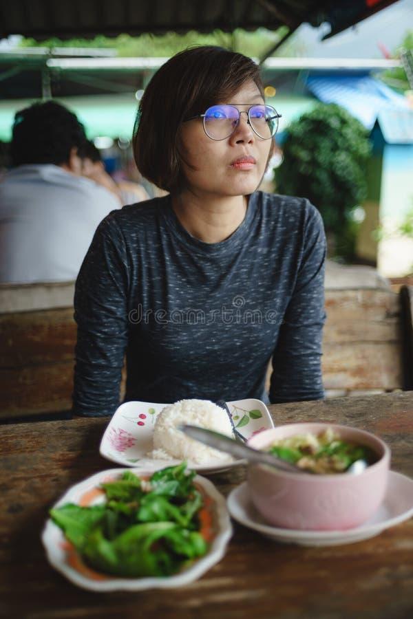 亚裔妇女用在桌上的食物在餐馆 库存图片