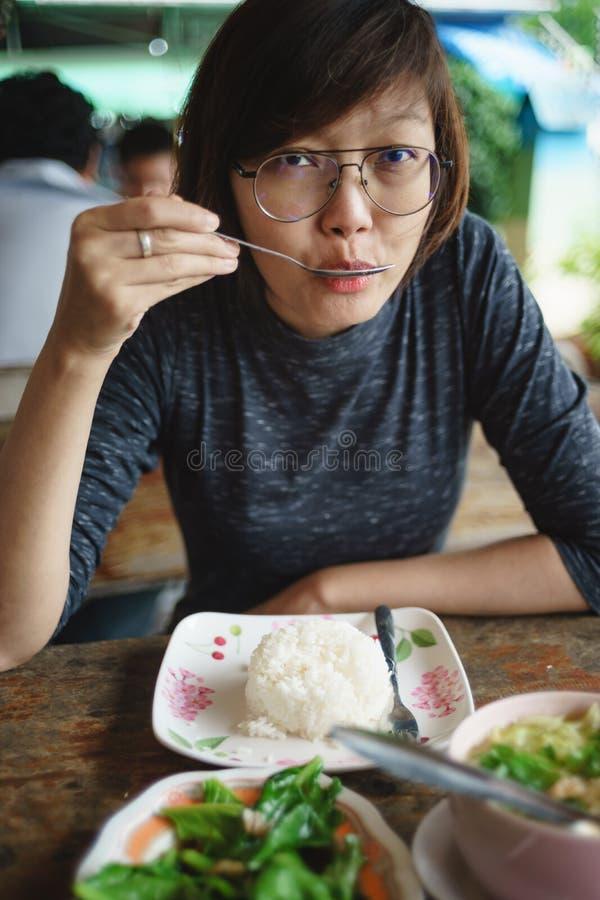 亚裔妇女用在桌上的食物在餐馆 库存照片