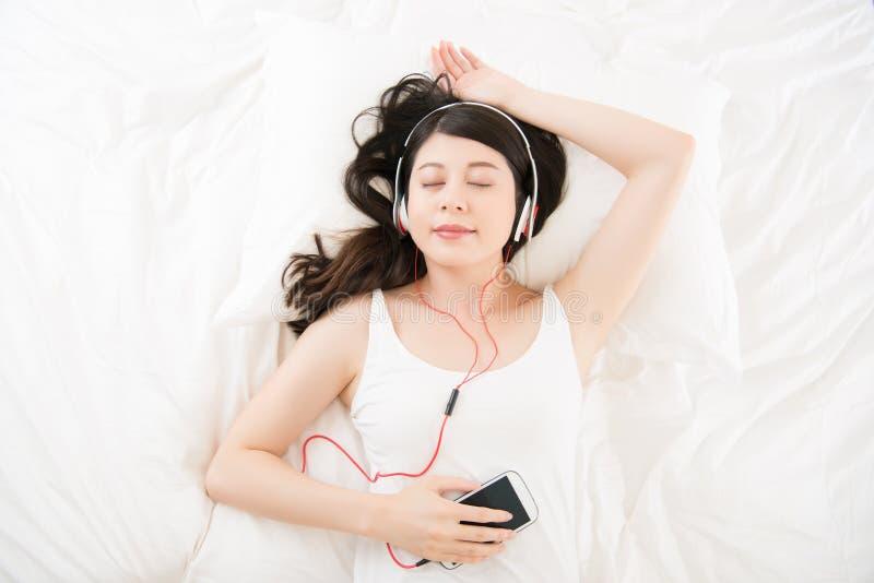 亚裔妇女由有耳机的巧妙的电话享受音乐 床 免版税图库摄影