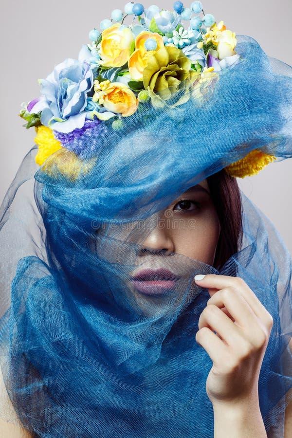 亚裔妇女画象有花卉看在浅灰色的背景的帽子和蓝色面纱的照相机 免版税库存图片