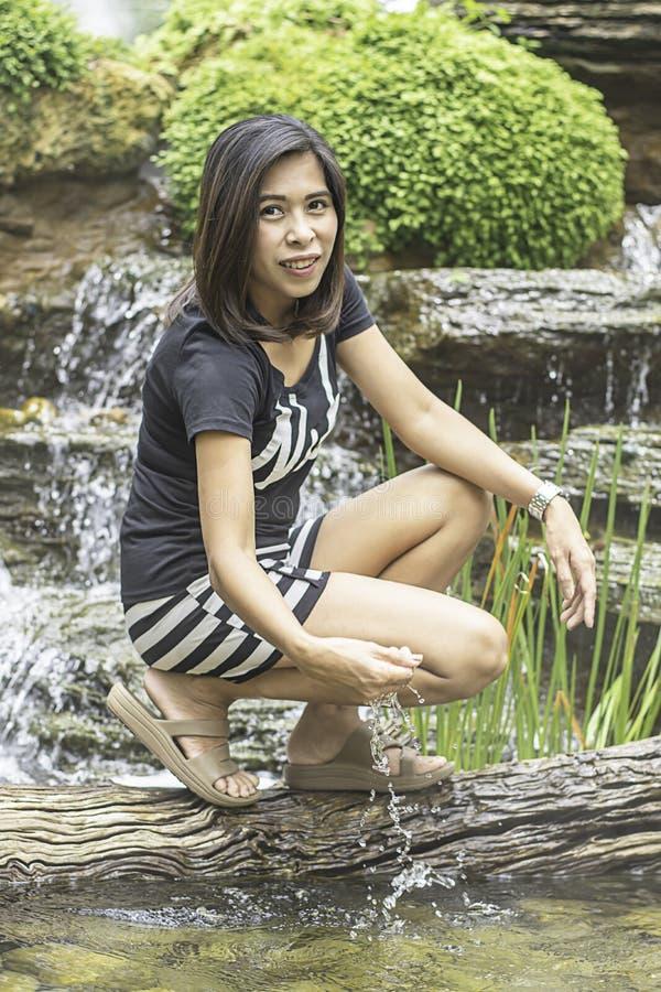 亚裔妇女画象用从瀑布的水使用 免版税库存图片