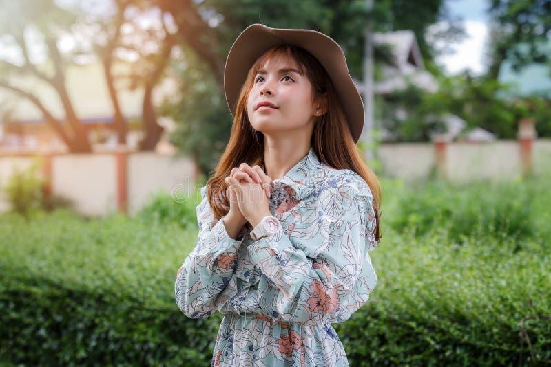 亚裔妇女相信祷告给上帝 俏丽的女孩在被弄脏的公园背景做愿望行动 图库摄影