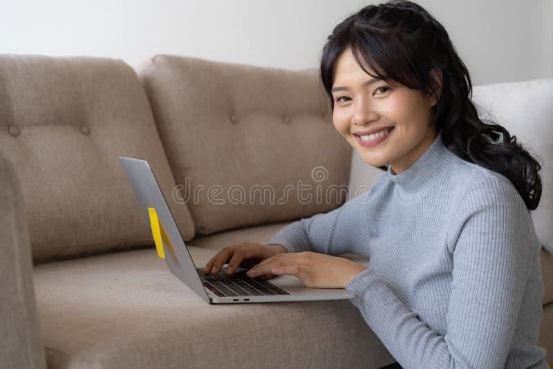 亚裔妇女研究一台膝上型计算机在客厅 她坐地板,并且沙发是办公桌 在她的面孔是微笑和 免版税库存照片