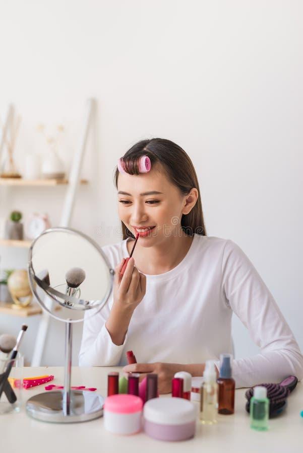 亚裔妇女秀丽博客作者,应用唇膏的vlogger于她的做化妆构成讲解的嘴 库存图片