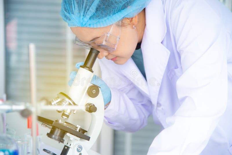 亚裔妇女科学家、研究员、技术员或者学生做了研究或试验通过使用显微镜在实验室 库存照片