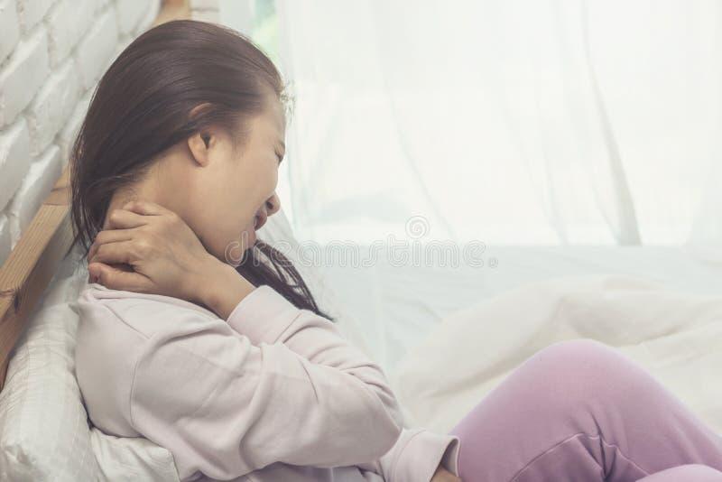 亚裔妇女背部疼痛和坐床 免版税库存图片
