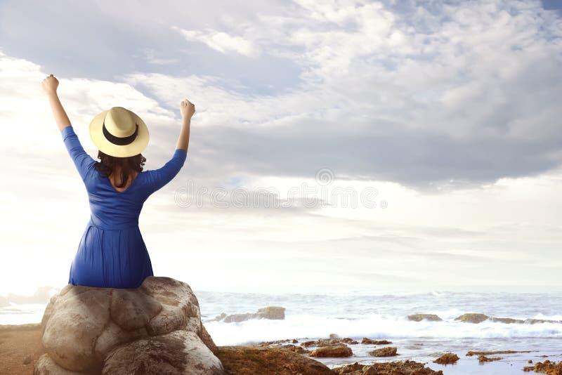 亚裔妇女背面图坐岩石和看海景的帽子的 库存照片