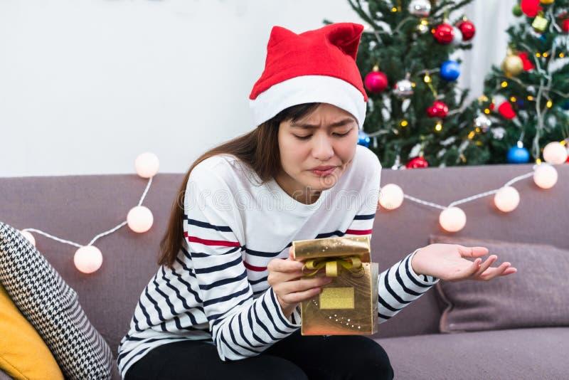 亚裔妇女让烦恼,当开放金子xmas礼物盒在沙发,乏味圣诞晚会礼物的节日晚会 免版税库存照片
