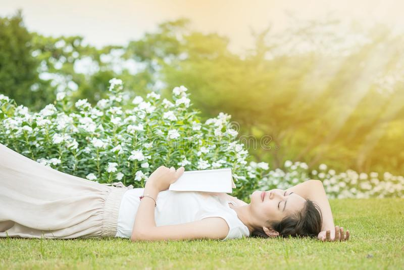 亚裔妇女说谎的草地,在她为读书疲倦了一本书下午后 图库摄影