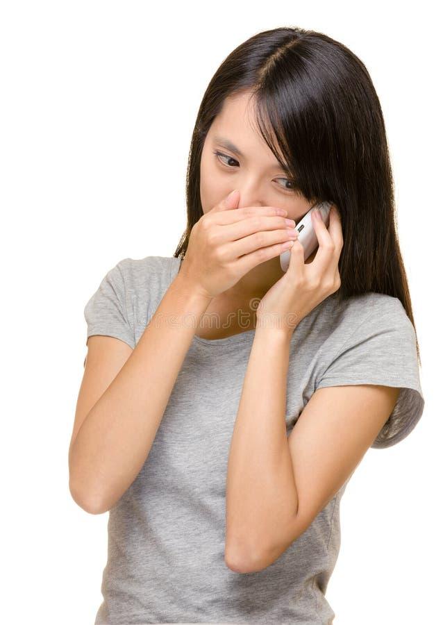 亚裔妇女谈的电话秘密地 库存图片