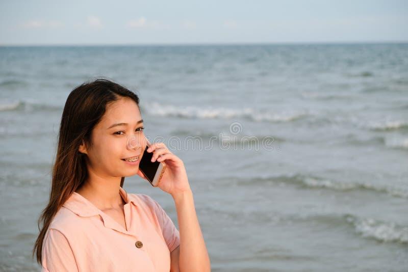 亚裔妇女谈话在海滩的手机身分,技术旅行 免版税库存图片