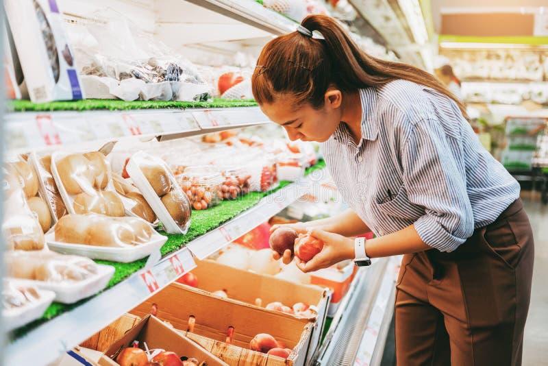 亚裔妇女购物的健康食品蔬菜和水果在超级市场 免版税库存图片
