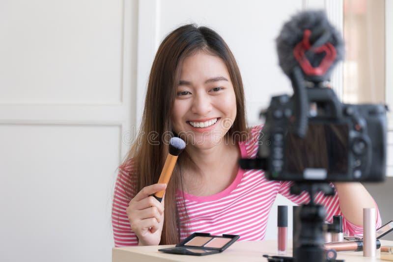 亚裔妇女通过直播,Blogg提供化妆用品 库存照片