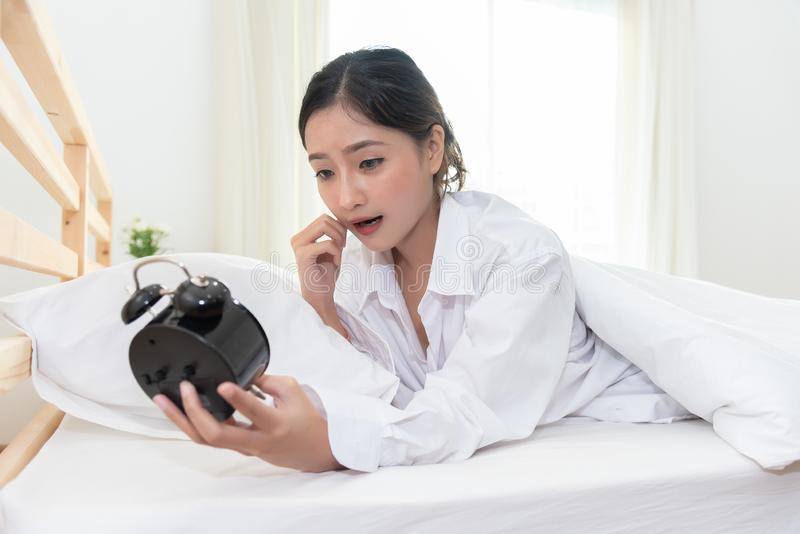 亚裔妇女震惊,当后醒忘记到设置警报 免版税库存照片