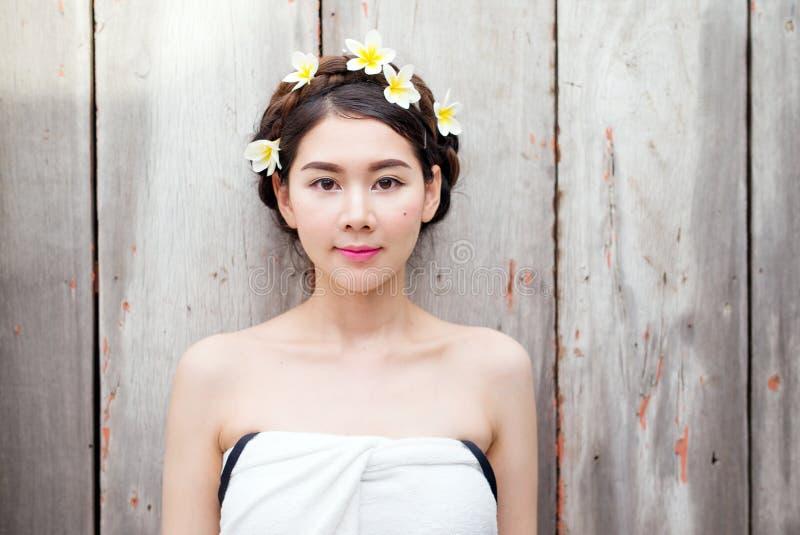 亚裔妇女面对美丽有在头的花 图库摄影