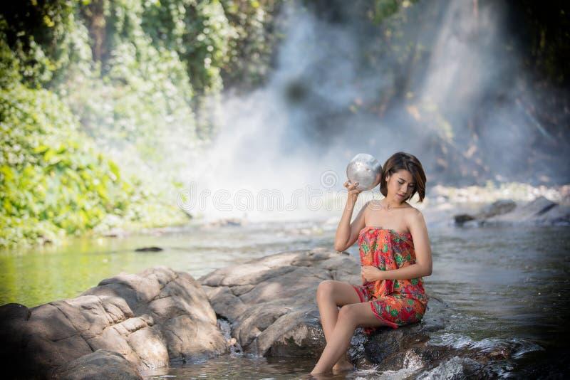 亚裔妇女洗在瀑布,泰国的浴 免版税库存照片