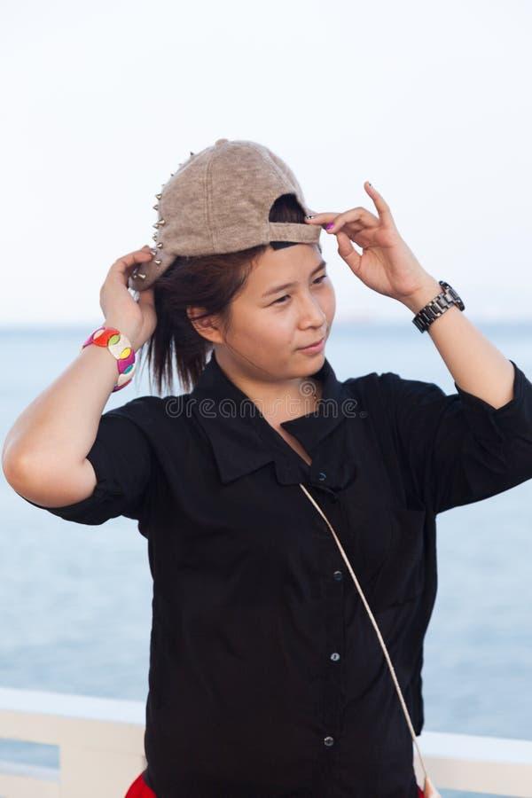 亚裔妇女黑衬衣。她戴帽子 免版税图库摄影