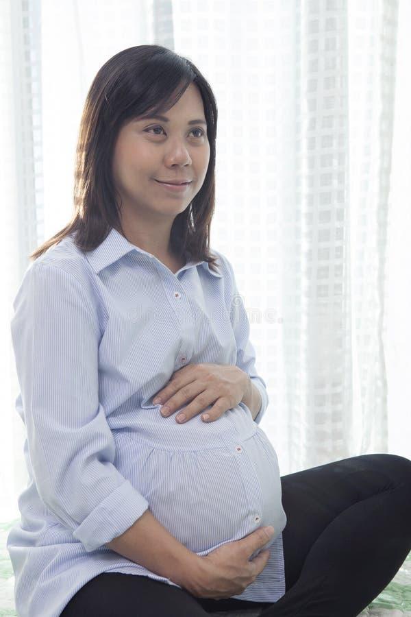 年轻亚裔妇女preginant开会在有机会的家庭客厅 免版税库存照片