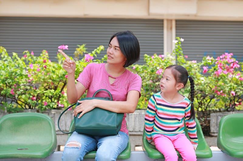 亚裔妈妈和她的女儿坐公共交通工具公共汽车 指向某事的妈妈儿童女孩看 图库摄影