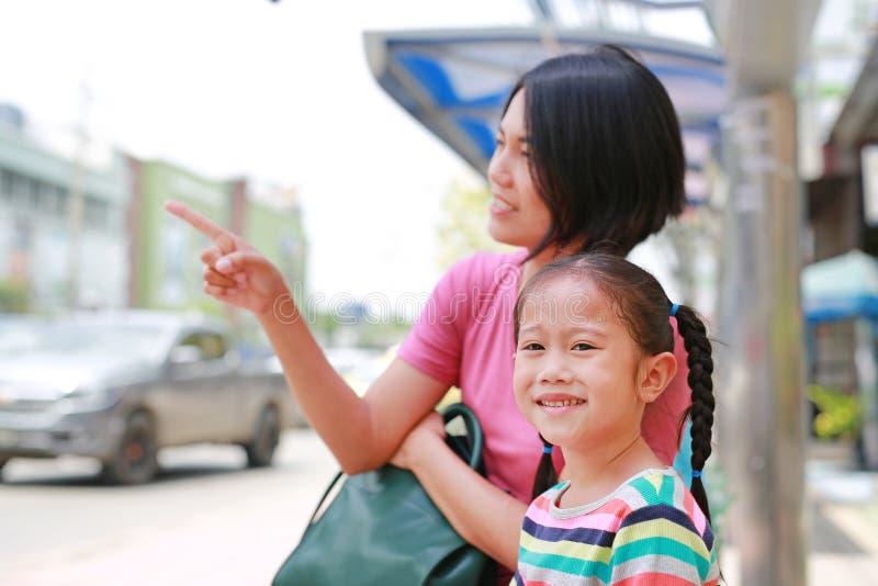 亚裔妈妈和她的女儿坐公共交通工具公共汽车 指向某事的妈妈儿童女孩看 库存照片