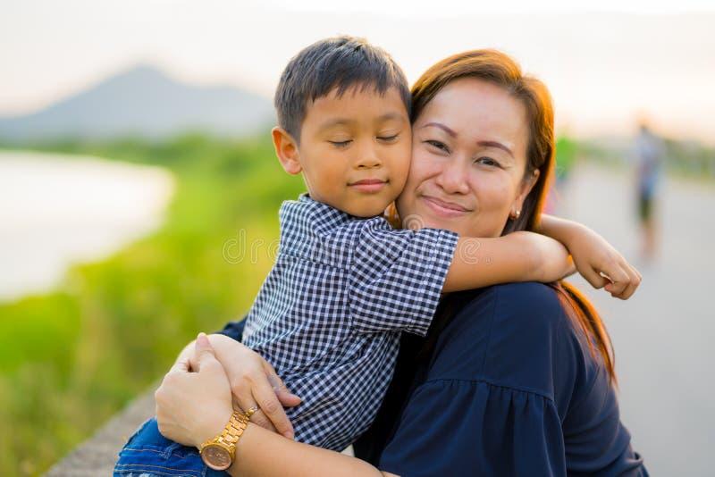 亚裔妈妈爱恋拥抱她的年轻儿子在与自然backg的日落 库存照片