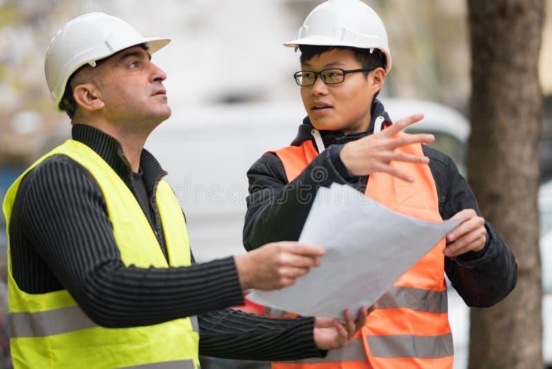 亚裔学徒工程师在建造场所的工作有高级管理人员的 库存照片