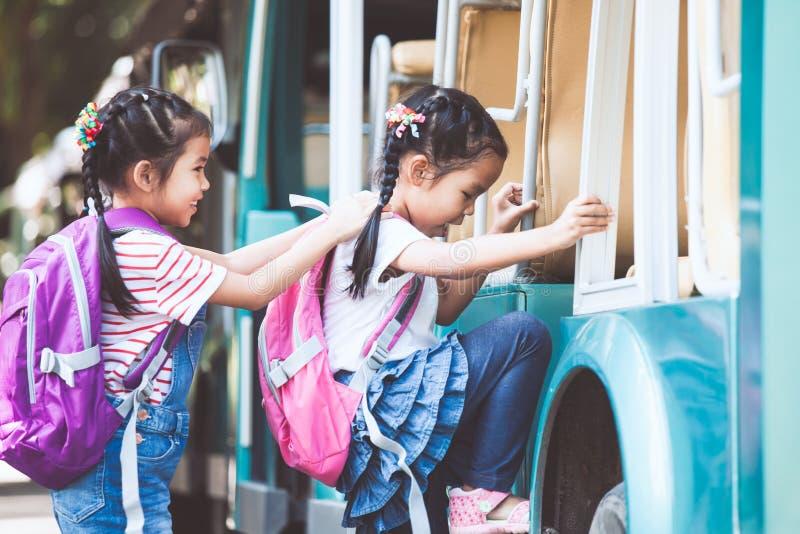 亚裔学生哄骗与握手和上学的背包 库存照片