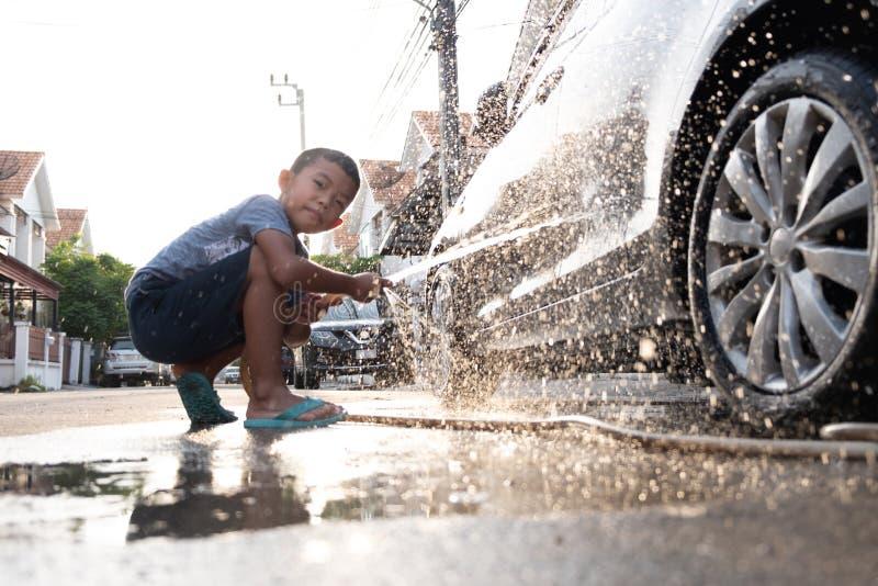 亚裔孩子使用水水管到洗涤的汽车 免版税库存照片
