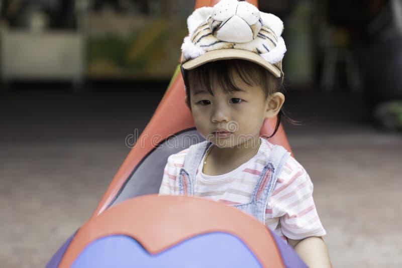 亚裔孩子女孩是在汽车玩具的幸福 免版税库存照片