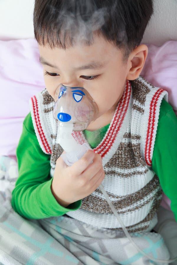 亚裔孩子拿着哮喘的治疗的一台面具蒸气吸入器 库存照片