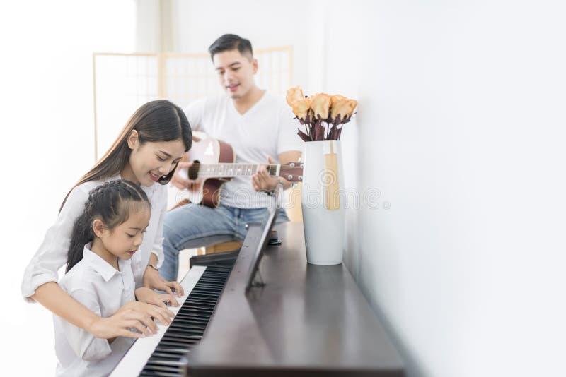 亚裔家庭、弹钢琴,父亲使用的母亲和女儿 库存照片