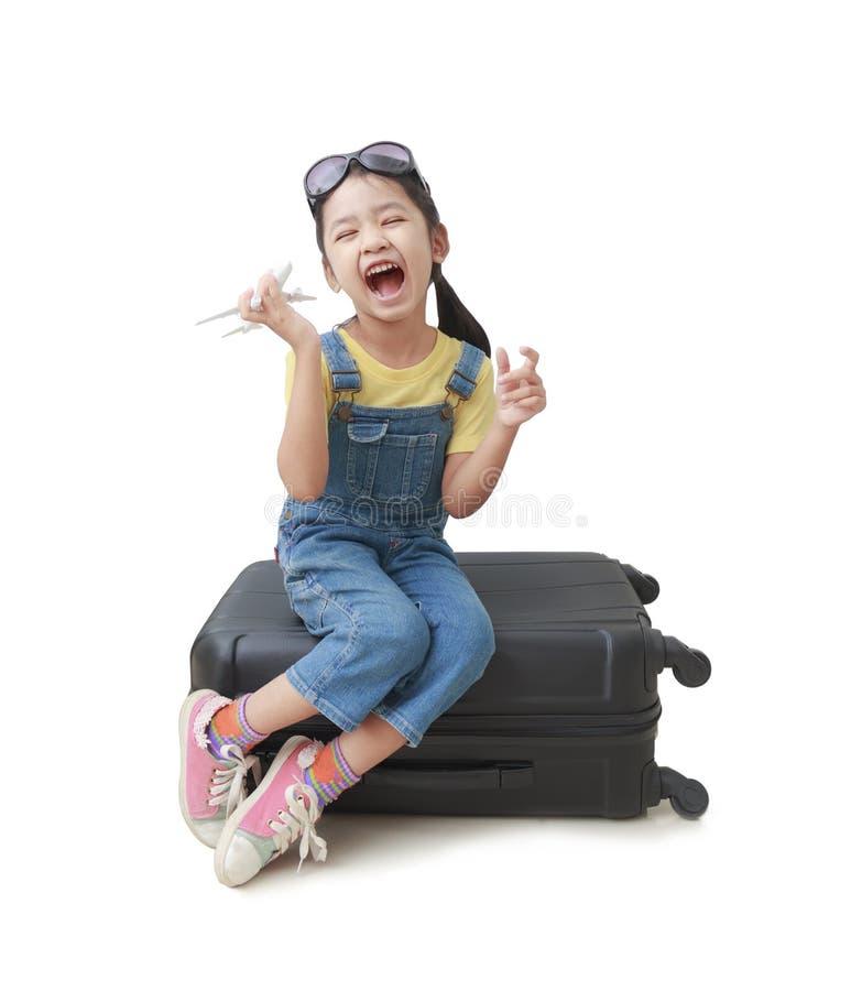 亚裔小女孩在她的手上拿着一架飞机并且坐她的lugg 库存照片