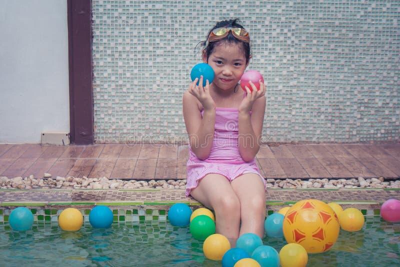 亚裔小女孩坐水池边缘、拿着小球的佩带的桃红色swimminh衣服和她的手 库存图片