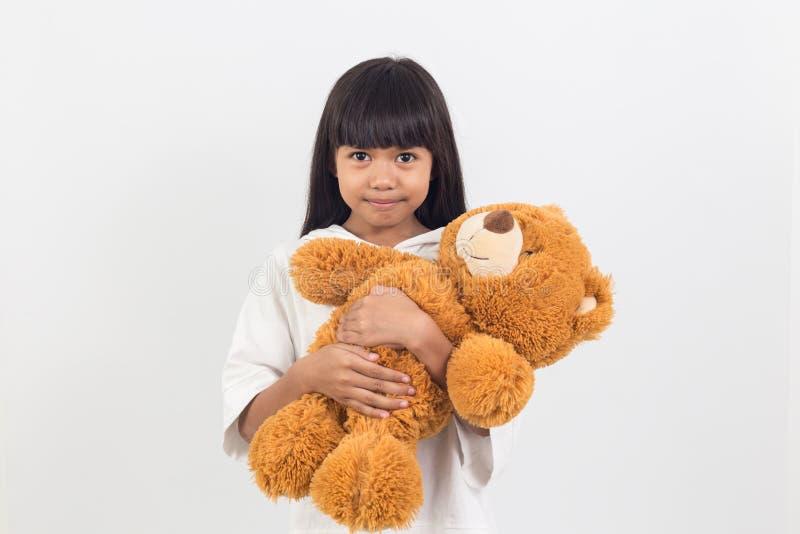 亚裔小女孩拥抱一件女用连杉衬裤涉及白色 免版税库存照片