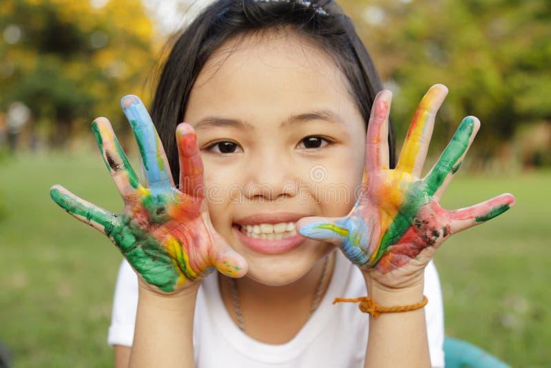 女孩用在五颜六色的油漆绘的手 图库摄影