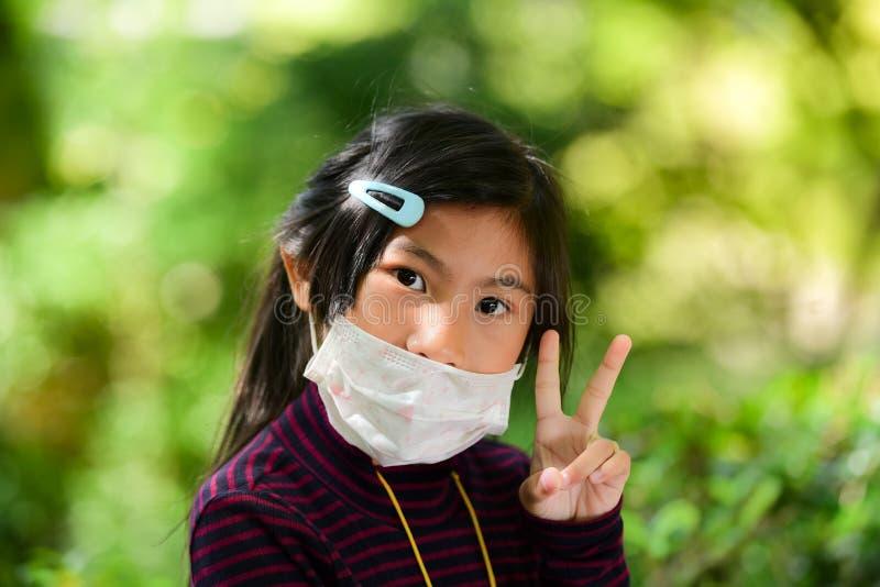 亚裔小女孩病与绿色bokeh 免版税库存图片