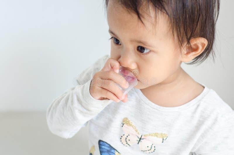 亚裔小女孩采取医学糖浆由她自己 免版税库存照片