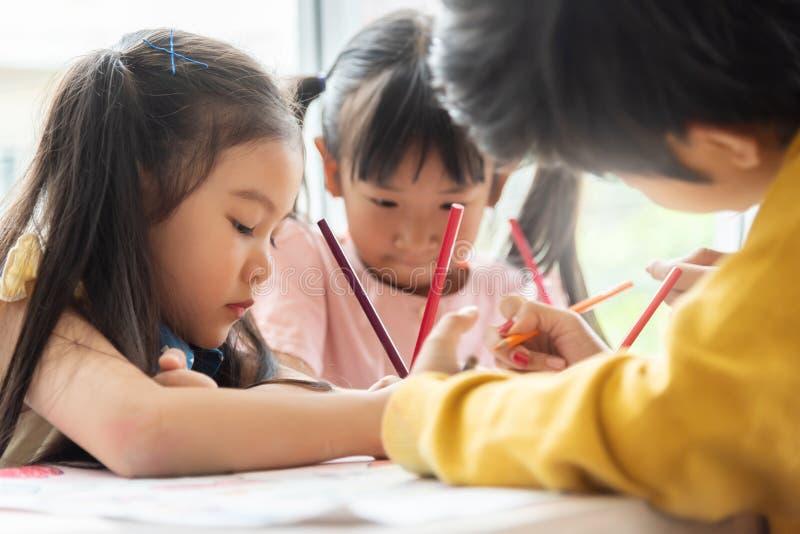 亚裔小孩在教室上色 图库摄影