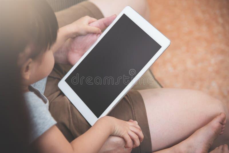 亚裔小孩女孩和她的家庭开会和使用数字式t 免版税库存图片