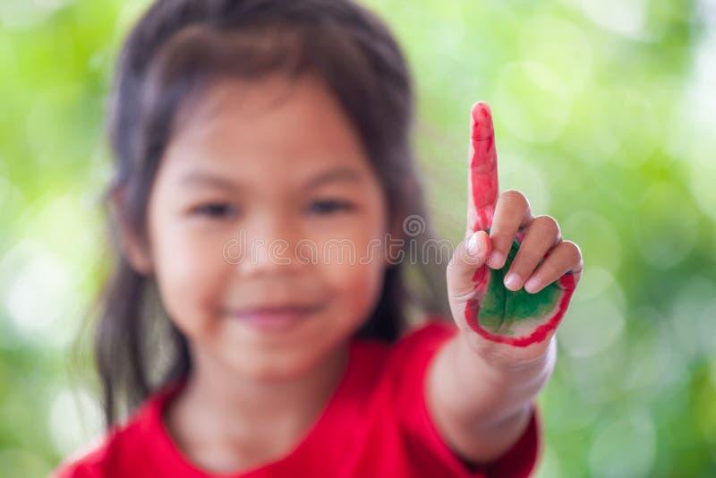 亚裔小孩女孩用显示手指的被绘的手第一 免版税图库摄影