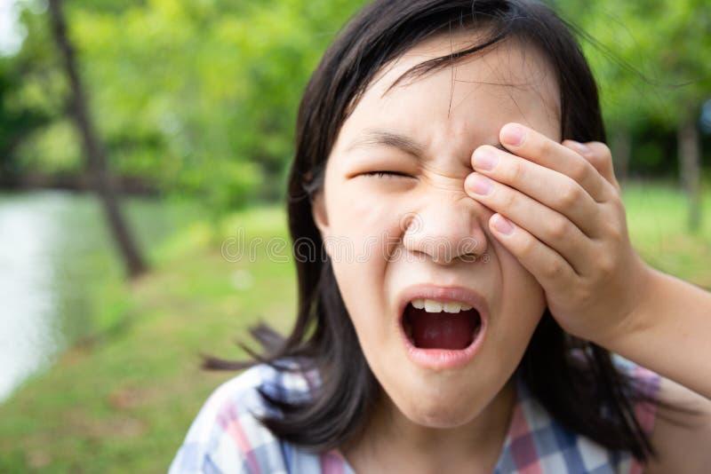 亚裔小孩女孩耐心痛苦,疼痛眼睛,接触,盖用手或摩擦她的眼睛,感觉的眼睛痛苦,女性有 免版税库存图片