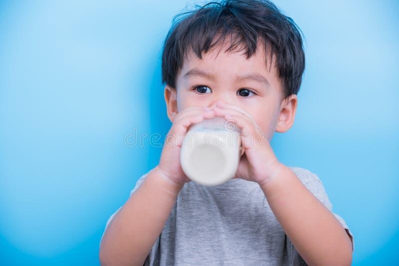 亚裔小孩男孩大约2从玻璃瓶的年饮用奶  免版税库存图片