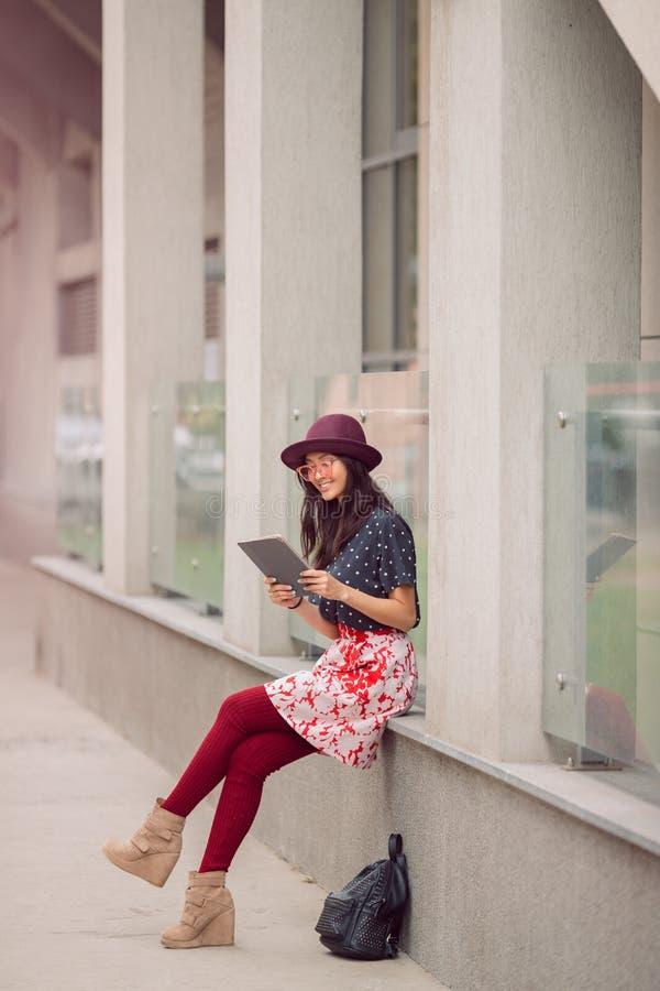 亚裔少妇与在城市街道的片剂计算机一起使用 免版税库存图片