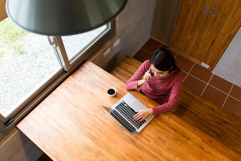 亚裔少妇在巧妙的电话做一个电话和工作在笔记 库存照片